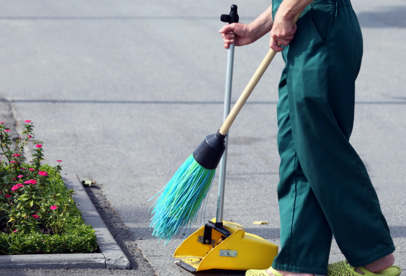 Closeup of a janitor in uniform using a commercial broom and long-handle standin