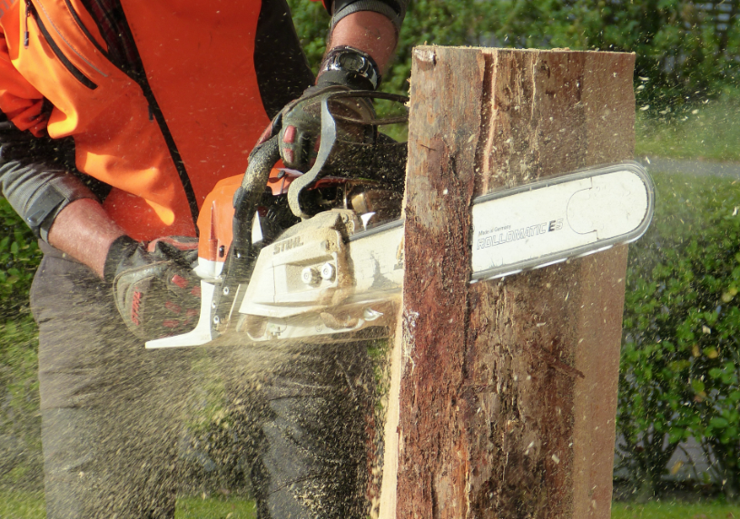 Chainsaw operator wearing a safety vest and gloves while cutting wood on a jobsite
