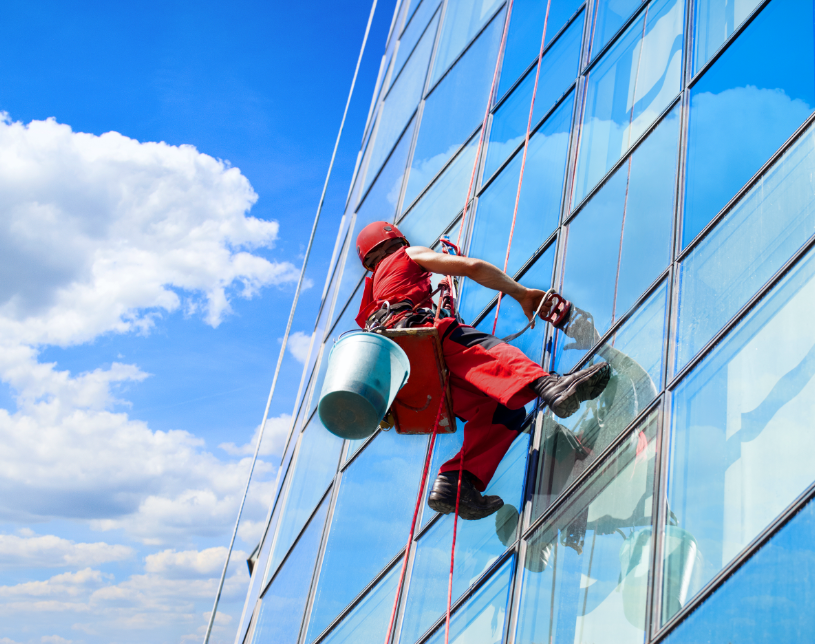 Cleaning professional wearing a safety harness while washing windows on the outs